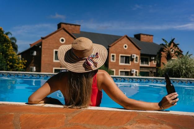 Jovem e bela mulher relaxando à beira da piscina com uma garrafa de cerveja.