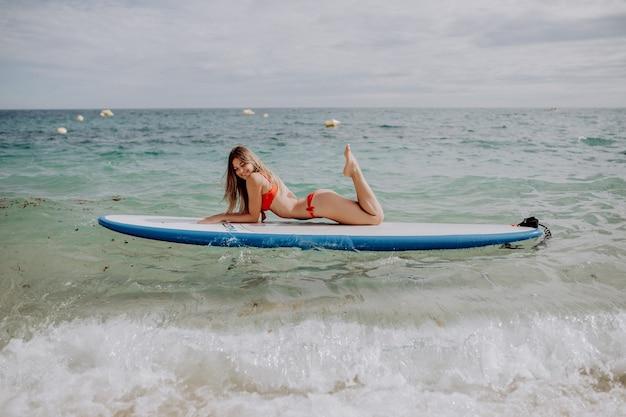 Jovem e bela mulher relaxante no mar em uma prancha de sup.