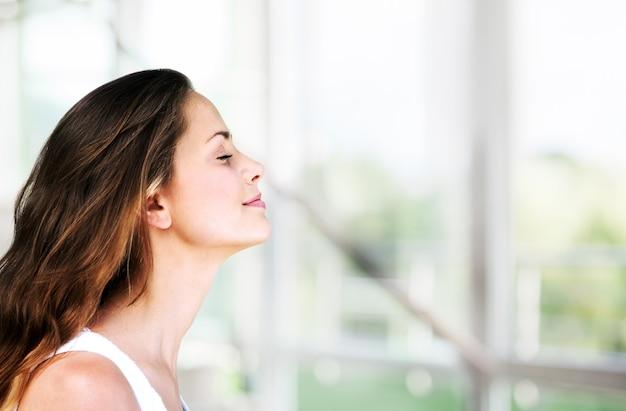 Jovem e bela mulher respirando ao ar livre com turva