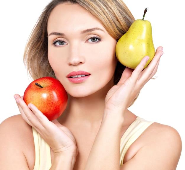 Jovem e bela mulher segura a maçã e a pêra - isoladas no branco.
