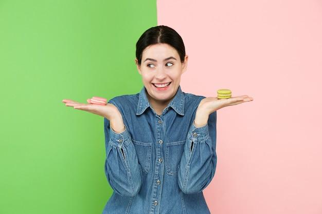 Jovem e bela mulher segurando confeitos de pastelaria nas mãos dela