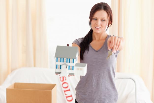 Jovem e bela mulher segurando modelo de casa e chaves