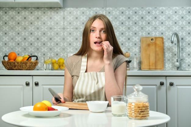 Jovem e bela mulher sentada à mesa na cozinha com uma tábua de cortar faca para produtos de frutas