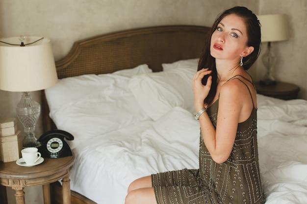 Jovem e bela mulher sentada na cama em um quarto de hotel, vestido de noite estiloso, glamour, sexy, roupa da moda, lençóis brancos