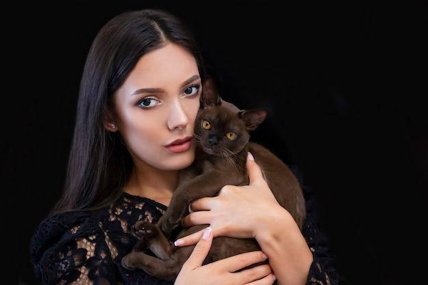 Jovem e bela mulher sexy com maquiagem brilhante e um gato nas mãos