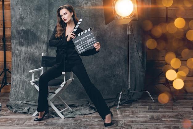Jovem e bela mulher sexy elegante nos bastidores do cinema, segurando um badalo de filme