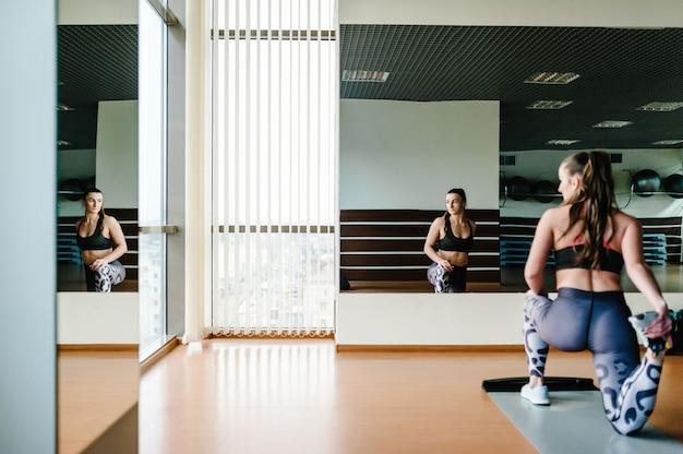 Jovem e bela mulher sexy em roupas esportivas fazendo alongamentos flexíveis das pernas, no chão, em um tapete na academia em frente ao espelho