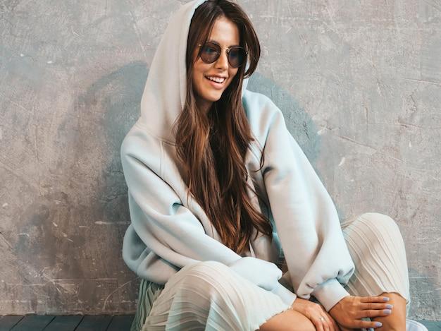 Jovem e bela mulher sexy olhando. menina na moda em roupas de verão casual capuz e saia. sentado no chão
