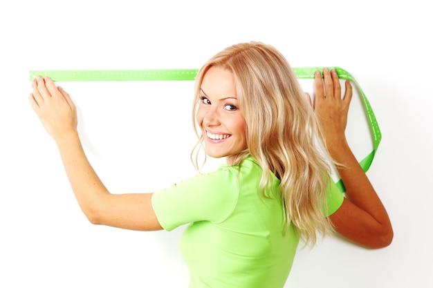 Jovem e bela mulher sorridente medindo espaçamento em uma parede com fita métrica verde, fundo branco