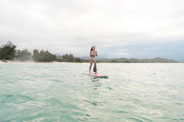 Jovem e bela mulher surfando no havaí