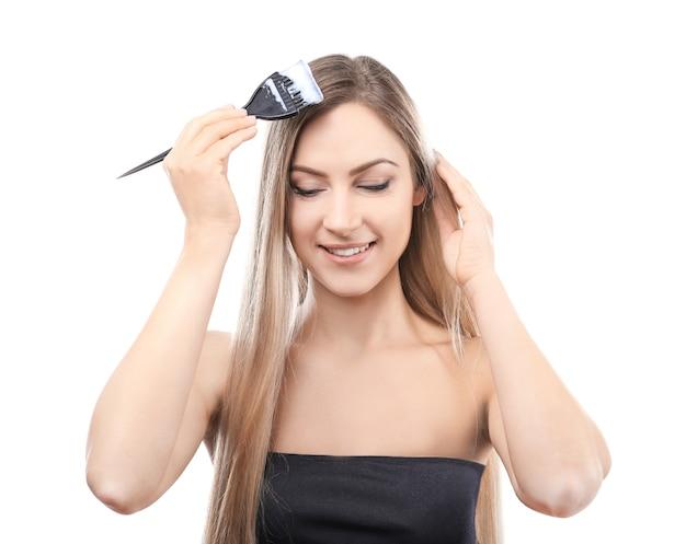 Jovem e bela mulher tingindo o cabelo em fundo branco