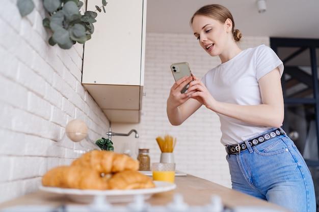 Jovem e bela mulher tirando foto no celular de croissants