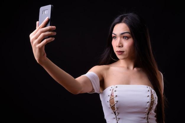 Jovem e bela mulher transgênero asiática contra negros