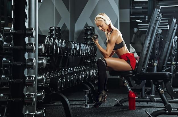 Jovem e bela mulher treinando no ginásio. conceito de fitness, treino, esporte, saúde