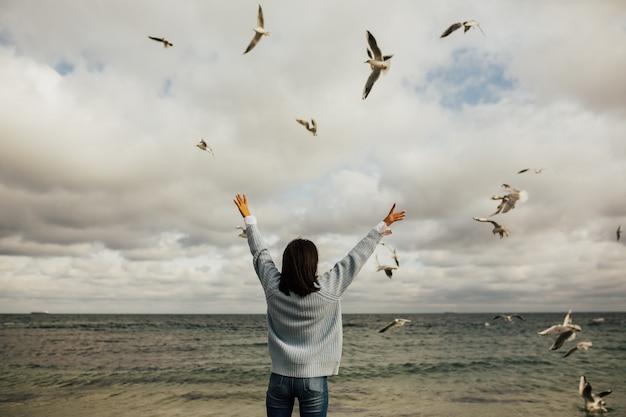 Jovem e bela mulher vendo as gaivotas voando - bando de pássaros.