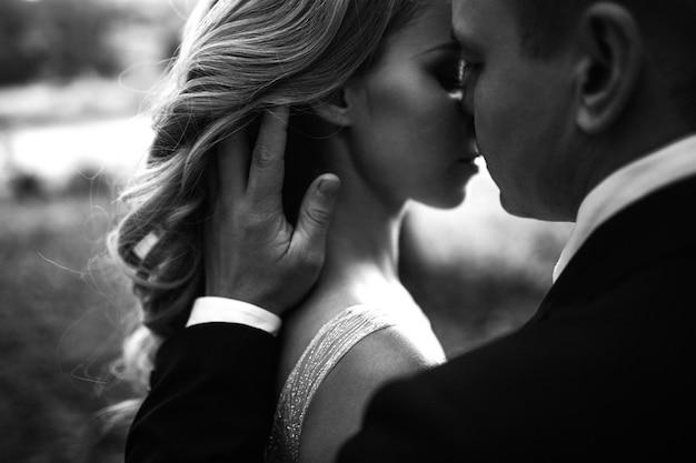 Jovem e bela noiva e o noivo se amam. na sombra de um véu voador.