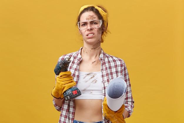 Jovem e bela trabalhadora usando óculos de proteção, luvas e camisa casual segurando uma máquina de perfuração e uma planta com olhar nojento franzindo a testa com relutância em consertar seu quarto