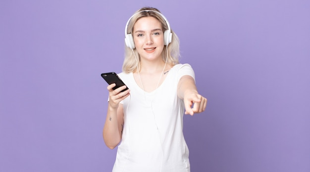 Jovem e bonita albina apontando para a câmera escolhendo você com fones de ouvido e smartphone