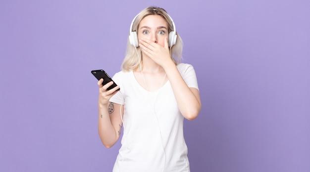 Jovem e bonita albina cobrindo a boca com as mãos com um choque com fones de ouvido e smartphone