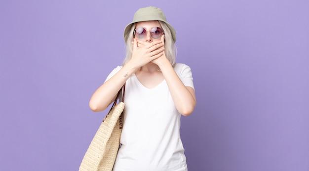 Jovem e bonita albina cobrindo a boca com as mãos com um choque. conceito de verão