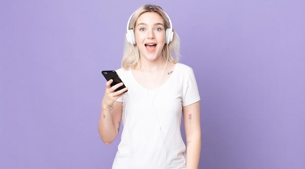 Jovem e bonita albina parecendo feliz e agradavelmente surpresa com fones de ouvido e smartphone
