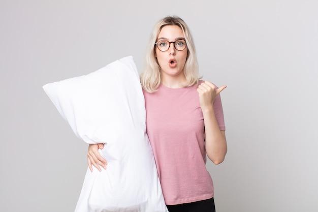 Jovem e bonita albina parecendo surpresa e descrente de pijama e segurando um travesseiro