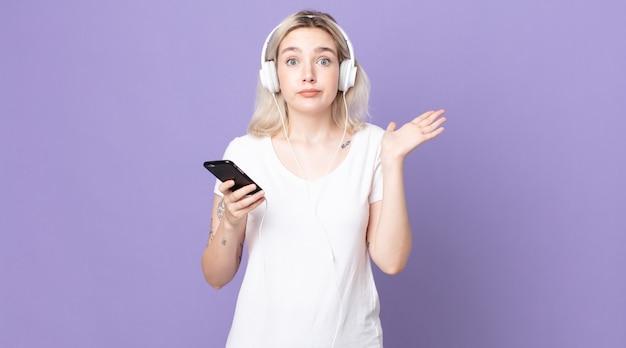Jovem e bonita albina se sentindo intrigada e confusa e duvidando com fones de ouvido e smartphone