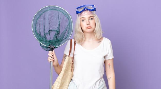 Jovem e bonita albina se sentindo triste e chorona com uma aparência infeliz e chorando com óculos de proteção e uma rede de pesca