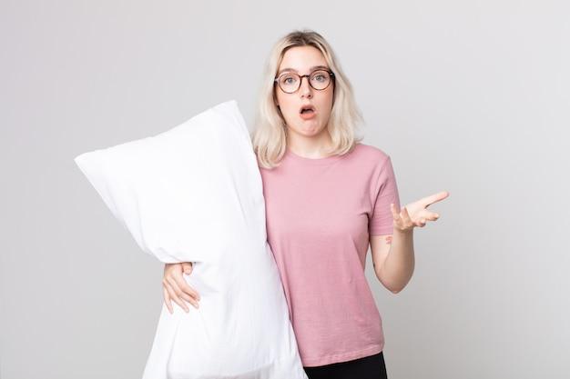Jovem e bonita albina sentindo-se extremamente chocada e surpresa de pijama e segurando um travesseiro