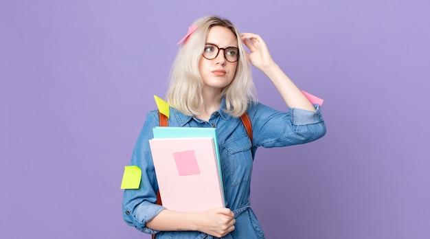 Jovem e bonita albina sentindo-se perplexa e confusa, coçando a cabeça. conceito de estudante
