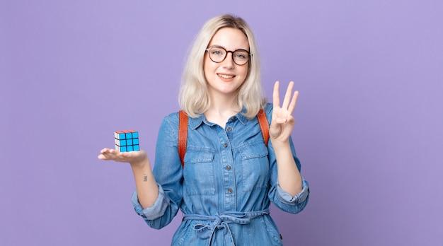 Jovem e bonita albina sorrindo e parecendo amistosa, mostrando o número três e resolvendo um jogo de inteligência