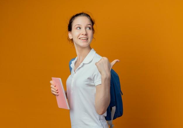 Jovem e bonita aluna alegre vestindo uma bolsa traseira em pé na vista de perfil, segurando um bloco de notas, olhando e apontando para trás, isolado em um fundo laranja com espaço de cópia