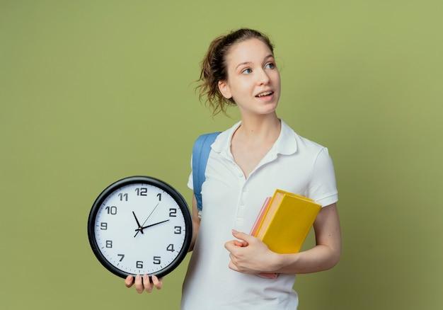 Jovem e bonita aluna impressionada com uma bolsa de costas, olhando para o lado, segurando um livro e um bloco de notas com um relógio isolado em um fundo verde com espaço de cópia