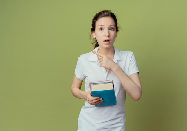 Jovem e bonita aluna impressionada segurando um livro e um bloco de notas apontando para o lado isolado em um fundo verde oliva com espaço de cópia