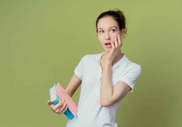 Jovem e bonita aluna impressionada segurando um livro e um bloco de notas, colocando a mão no rosto e olhando para o lado isolado em um fundo verde oliva com espaço de cópia