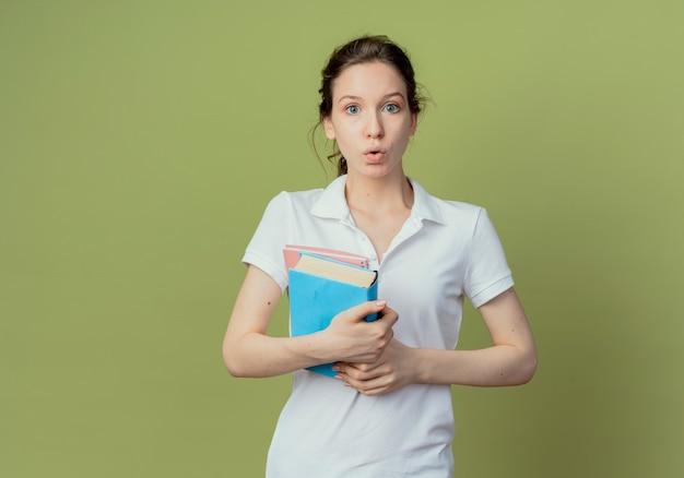 Jovem e bonita aluna impressionada segurando um livro e um bloco de notas isolados em um fundo verde oliva com espaço de cópia