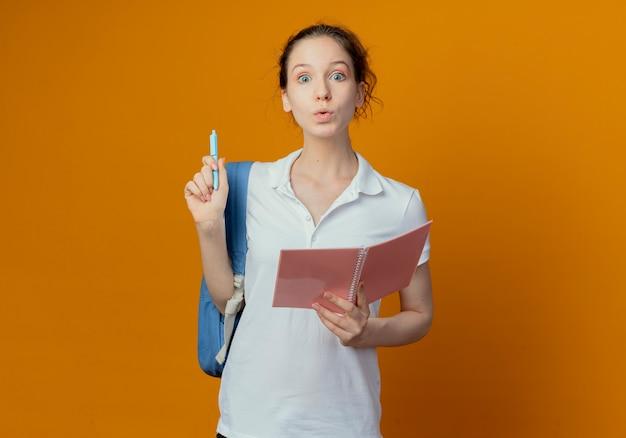 Jovem e bonita aluna impressionada usando uma bolsa com um bloco de notas aberto e uma caneta