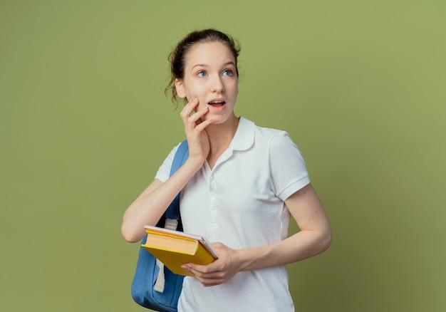 Jovem e bonita aluna impressionada vestindo uma bolsa de costas segurando um caderno e um livro, colocando a mão no queixo e olhando para o lado isolado em um fundo verde oliva com espaço de cópia