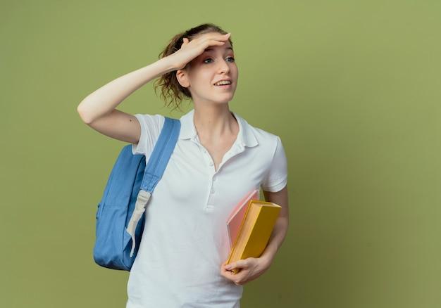 Jovem e bonita aluna impressionada vestindo uma bolsa de costas segurando um livro e um bloco de notas, olhando a distância, isolada em um fundo verde oliva com espaço de cópia