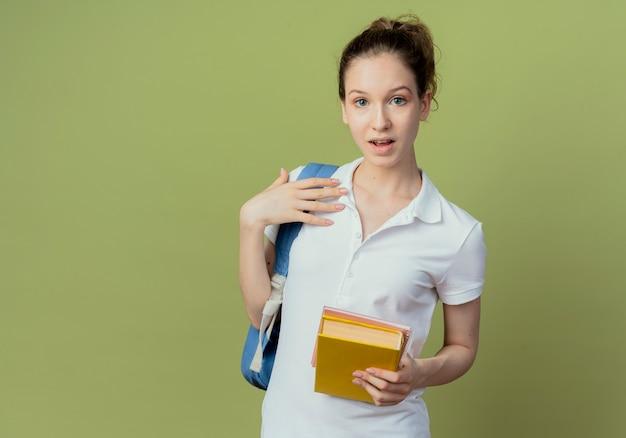 Jovem e bonita aluna impressionada vestindo uma bolsa de volta segurando um bloco de notas e um livro e tocando seu ombro isolado em um fundo verde oliva com espaço de cópia