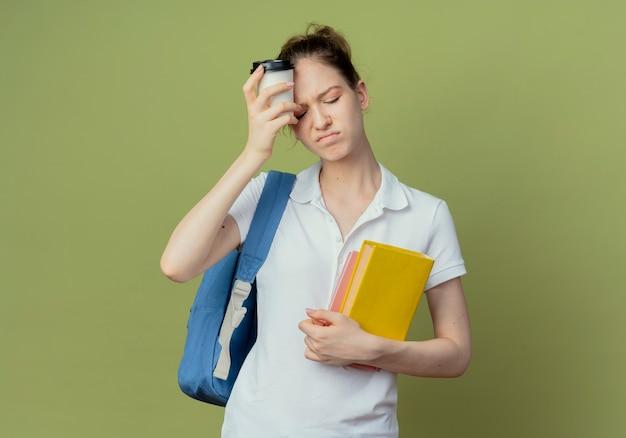 Jovem e bonita aluna insatisfeita vestindo uma bolsa com um livro e um bloco de notas e tocando a testa com uma xícara de café de plástico isolada em um fundo verde com espaço de cópia