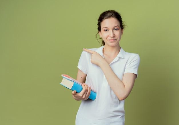 Jovem e bonita aluna satisfeita segurando um livro e um bloco de notas apontando para o lado isolado em um fundo verde oliva com espaço de cópia