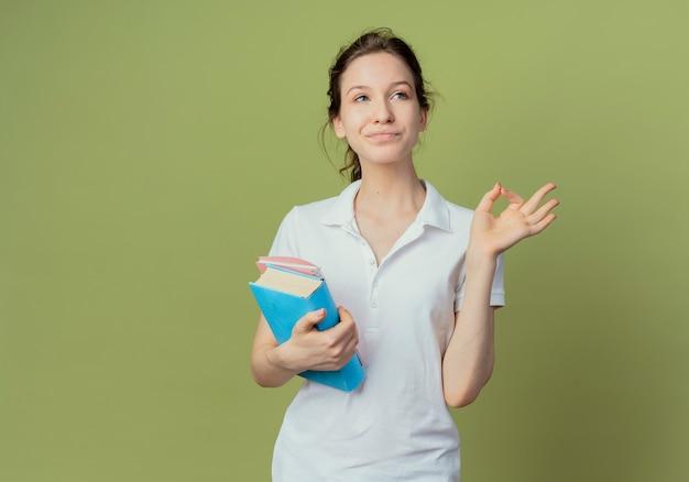 Jovem e bonita aluna satisfeita segurando um livro e um bloco de notas, olhando para o lado e fazendo sinal de ok, isolado em um fundo verde oliva com espaço de cópia