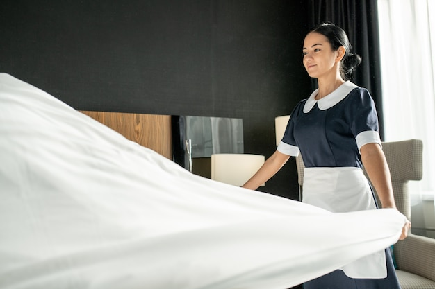 Jovem e bonita camareira sorridente colocando roupa de cama branca limpa enquanto troca de cama no quarto do hotel durante a preparação para novos hóspedes