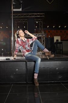 Jovem e bonita cantora pop star sorridente com microfone sentado em cena no clube