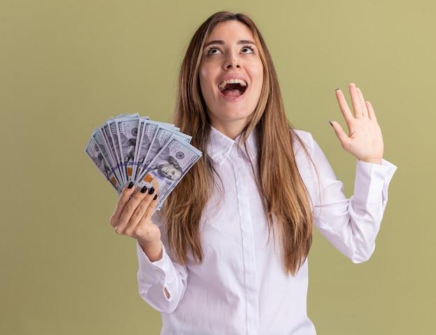 Jovem e bonita caucasiana animada com a mão levantada e segurando o dinheiro olhando para cima