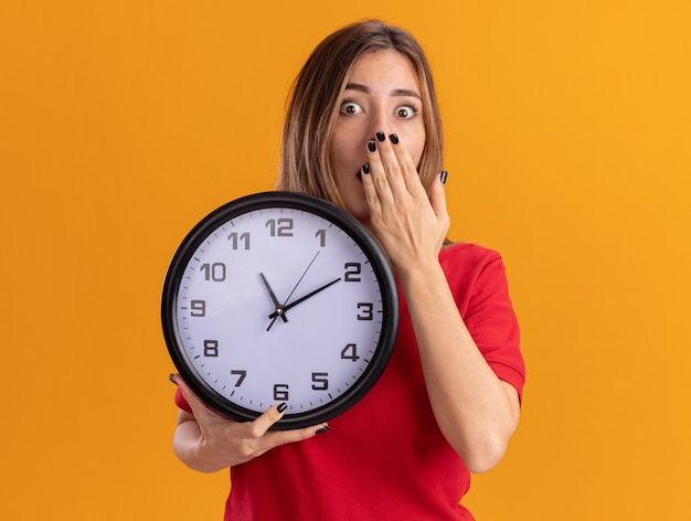 Jovem e bonita caucasiana chocada coloca a mão na boca e segura o relógio laranja