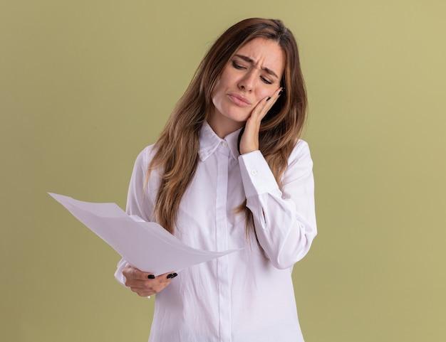 Jovem e bonita caucasiana insatisfeita coloca a mão no rosto, segurando e olhando para as folhas de papel em branco na cor verde oliva