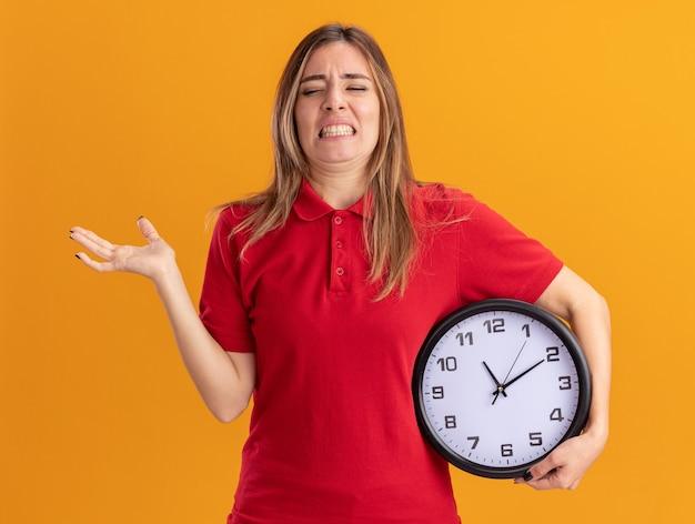 Jovem e bonita caucasiana insatisfeita segurando o relógio e a mão aberta na laranja