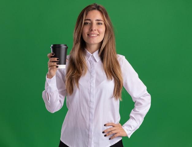 Jovem e bonita caucasiana sorridente coloca a mão na cintura e segura o copo de papel verde